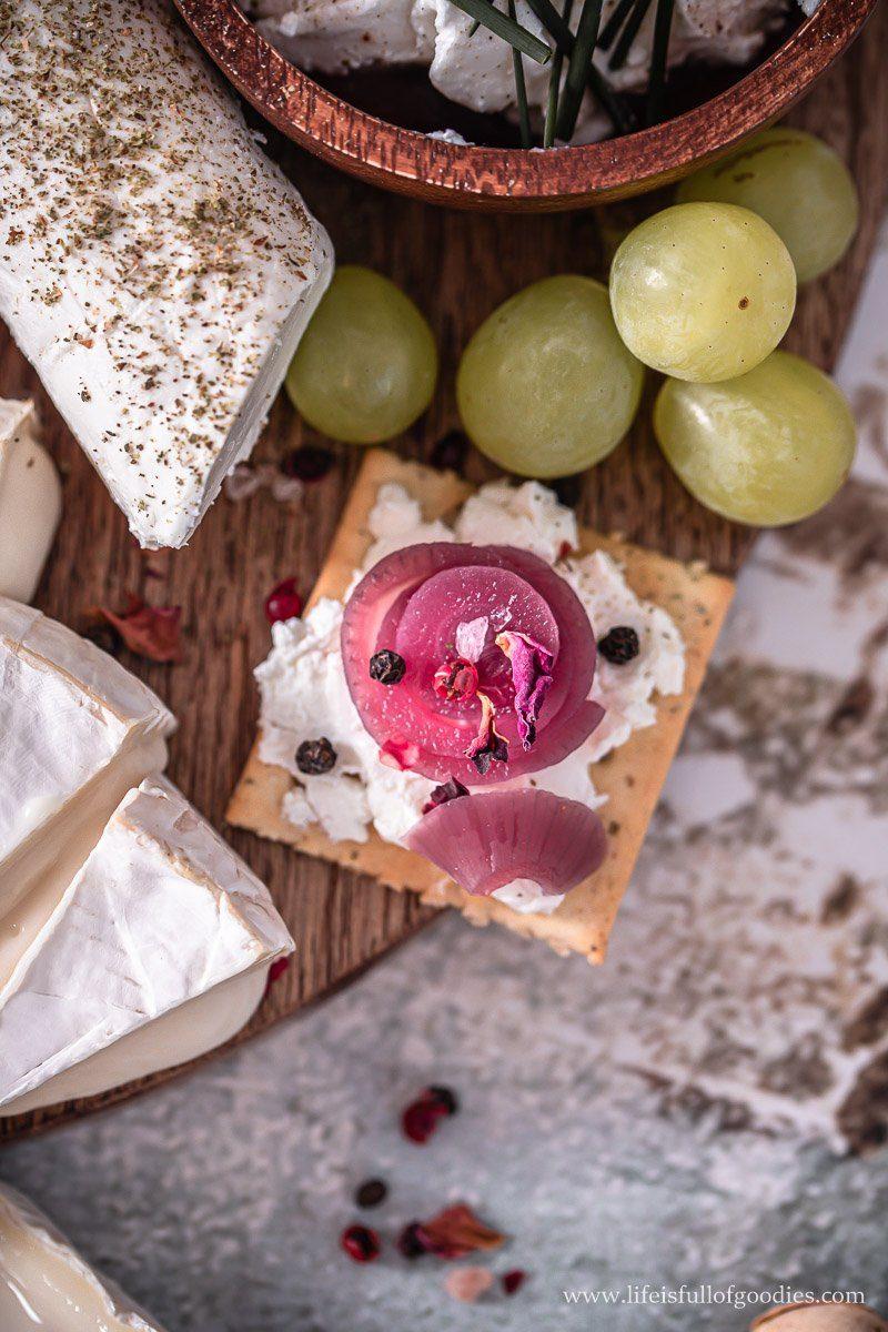Eine französische Ziegenkäseplatte mit eingelegten rosa Zwiebeln
